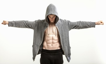 Body builder in hoodie with outstretched arms exposing abdominal muscle